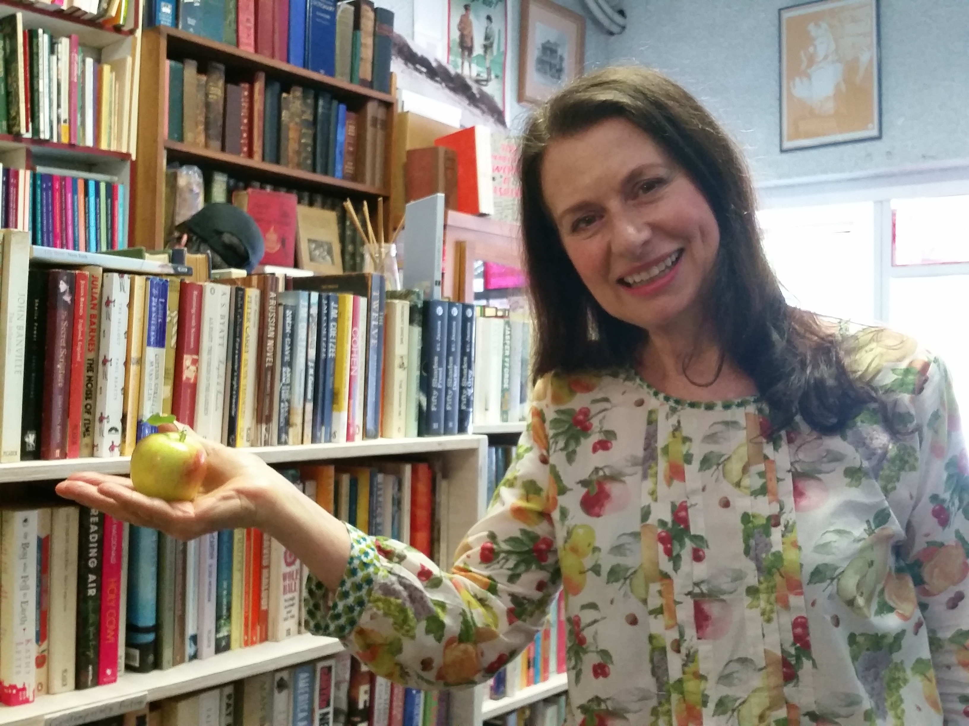 Suzie standing with a locally grown apple in Minerva's Bookstore