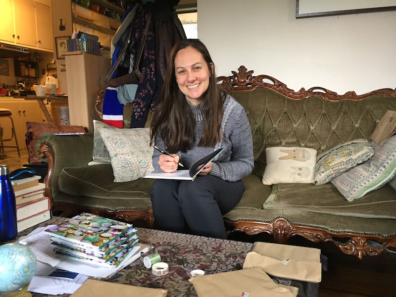 Amy Tsilemanis signing books on her couch